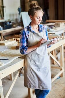 Femme, utilisation, tablette numérique, dans, boiseries, magasin