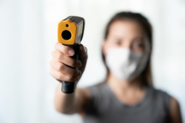 Femme, utilisation, thermomètre, vérifier, gens, protéger, corona, virus utilisez un thermomètre numérique pour vérifier la température.