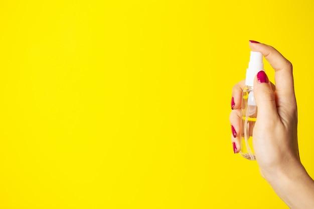 Femme utilise un antiseptique à la main sur fond jaune.
