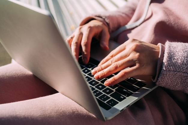 Une femme utilise un ordinateur portable dans la rue. travail à distance.