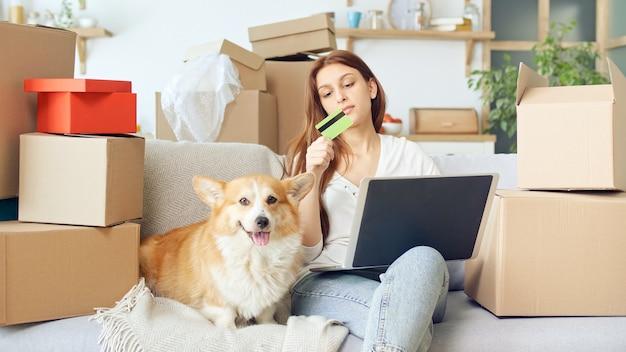 Une femme utilise un ordinateur portable pour faire des achats en ligne à la maison. confirmation d'achat par internet. relier une carte pour les achats en ligne. une femme assise sur le canapé avec un chien mignon lors de ses achats en ligne.