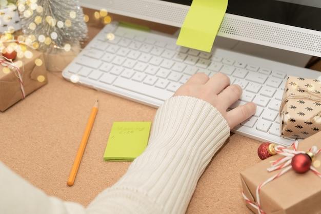 Femme utilise un ordinateur pour commander des cadeaux boîtes à cadeaux pour ordinateur décoration de vacances vente de vacances d'hiver