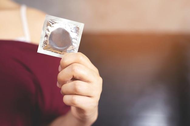 La femme utilise un préservatif pour prévenir le sida.