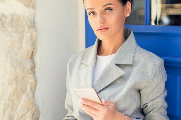 La femme utilise le smartphone à la porte