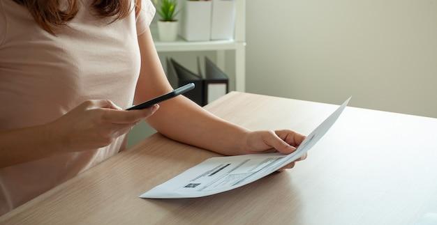 Une femme utilise un smartphone pour scanner le code-barres afin de payer ses factures de téléphone mensuelles après avoir reçu une facture envoyée à la maison. concept de paiement de factures en ligne