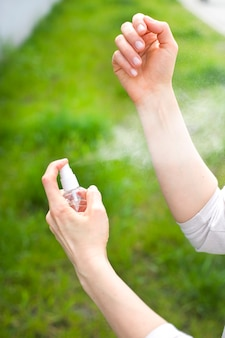 La femme utilise un spray insecticide et anti-moustique.