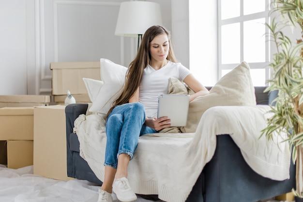 Femme utilise une tablette numérique dans son nouvel appartement