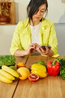 La femme utilise une tablette numérique ou un smartphone, cherche des recettes de cuisine dans la cuisine à la maison, un concept d'alimentation saine, végétalien ou diététique. épicerie en ligne