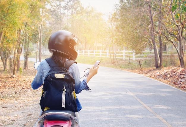 Femme utilise le téléphone et la moto en bordure de route.