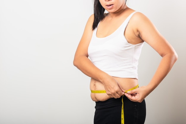 Femme utiliser la section cicatrice post-partum mesurer la taille des vergetures desserrer la peau du bas de l'abdomen
