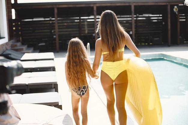 Femme avec des vacances d'ion fille. ils vont nager dans une piscine avec matelas gonflable en forme d'ananas.