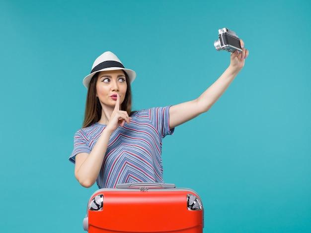 Femme en vacances tenant un appareil photo prenant une photo sur bleu