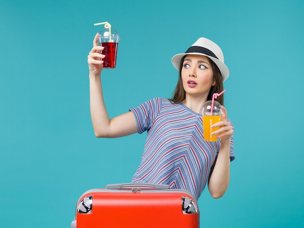 Femme en vacances tenant des boissons fraîches sur bleu
