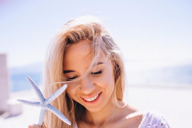 Femme en vacances tenant une étoile de mer