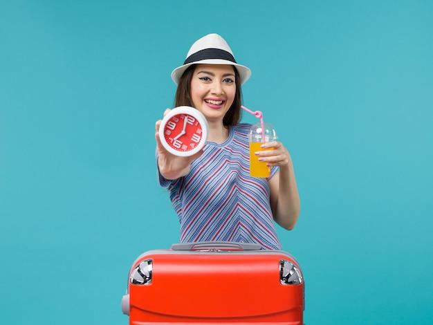 Femme en vacances tenant horloge et jus sur bleu