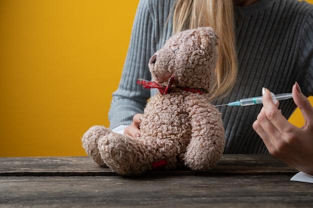 Femme vaccinant un ours en peluche