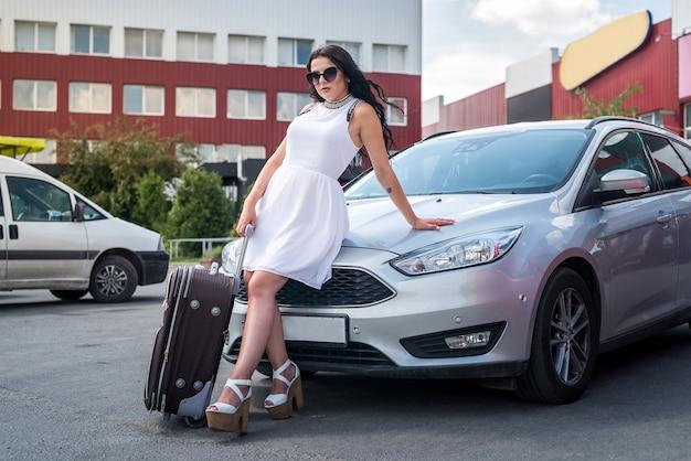 Femme avec valise assis sur le capot de la voiture