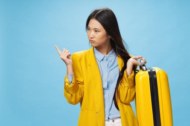 Femme avec valise jaune voyage voyage passager fond bleu