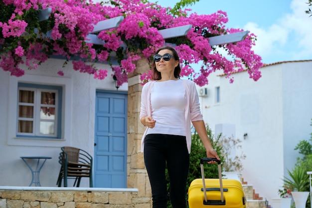 Femme avec valise marchant en plein air à travers le territoire de la mer pittoresque hôtel spa de villégiature avec un bel aménagement paysager de fleurs roses. voyages, vacances, loisirs, week-end, personnes
