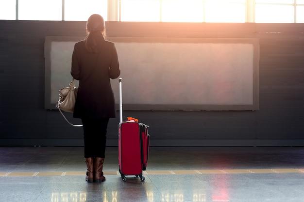 Femme avec valise rouge debout dans l'aéroport devant l'horaire de vol