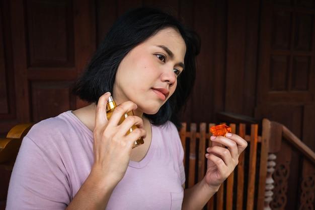 La femme vaporise du parfum sur son cou.