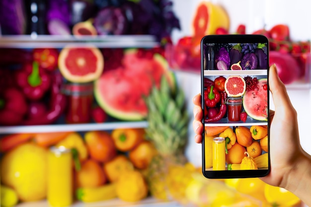 Femme végétarienne végétalienne femme prenant une photo d'aliments sains antioxydants colorés, de légumes, de jus cru et de fruits à manger dans le réfrigérateur: pamplemousse, tomates, pastèque, ananas par smartphone
