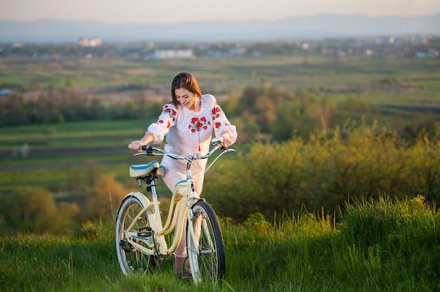 Femme avec vélo rétro sur la colline le soir