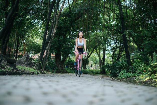 Femme, vélo route, dans parc portrait de belle jeune femme en vélo rose.