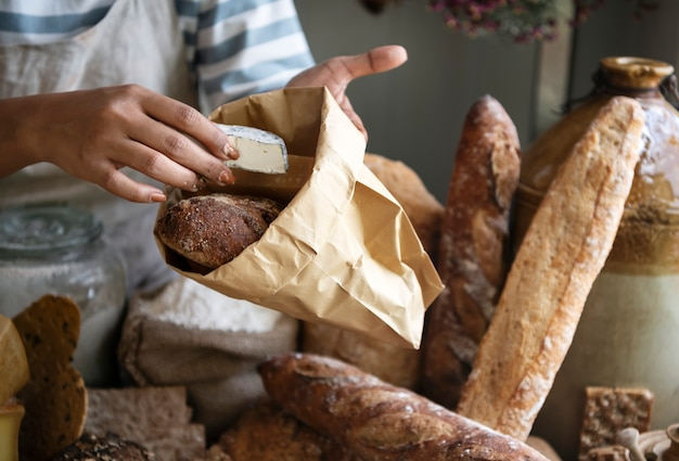Femme vendant du fromage à un client dans un magasin de la ferme