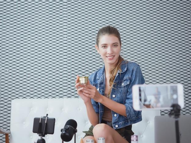 Femme vendant des produits de beauté en ligne, faisant des affaires chez elle