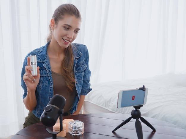 Femme vendant des produits de beauté en ligne avec ordinateur, faisant des affaires chez elle