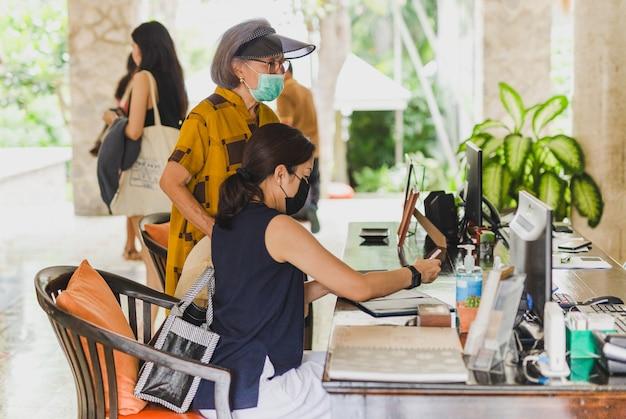 Femme vérifiant au comptoir de l'hôtel portant des masques médicaux contre le virus.