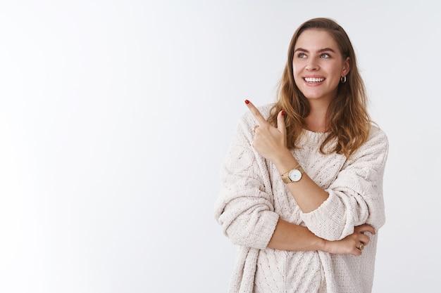 Femme vérifiant l'exposition d'un ami exprimant son opinion pointant du doigt l'air amusé ravi souriant largement discutant du produit, debout satisfait pose détendue, fond blanc insouciant