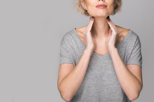Femme vérifiant la glande thyroïde par elle-même. gros plan d'une femme en t-shirt blanc touchant le cou avec une tache rouge. les troubles thyroïdiens comprennent le goitre, l'hyperthyroïdie, l'hypothyroïdie, la tumeur ou le cancer. soins de santé.