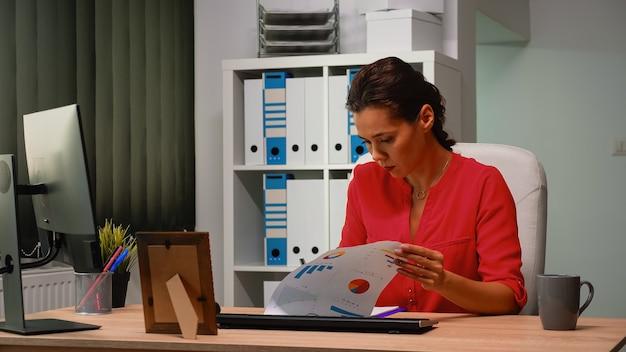 Femme vérifiant les graphiques devant l'ordinateur dans un bureau moderne à l'aide des informations du presse-papiers. entrepreneur travaillant dans l'espace de travail d'une entreprise professionnelle en tapant sur le clavier de l'ordinateur en regardant le bureau