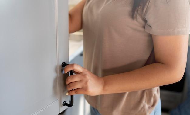 Femme vérifiant l'intérieur de son réfrigérateur à la maison