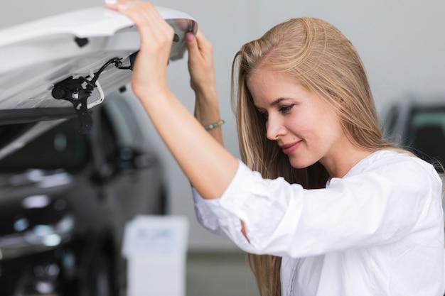 Femme vérifiant le moteur de sa voiture