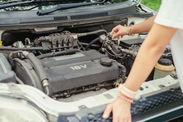 Femme vérifiant le moteur de la voiture avant le voyage