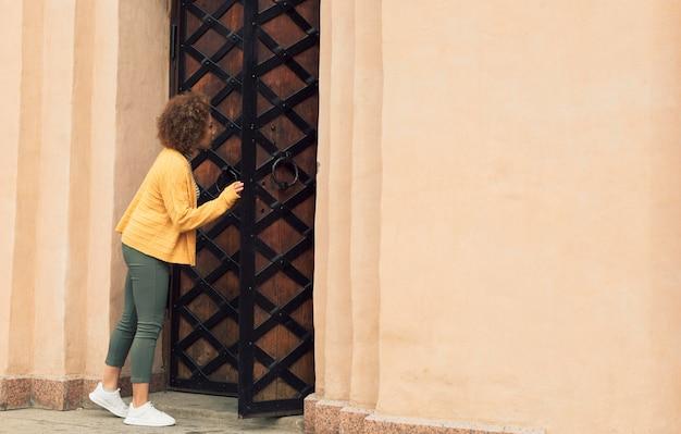 Femme vérifiant une porte avec espace copie