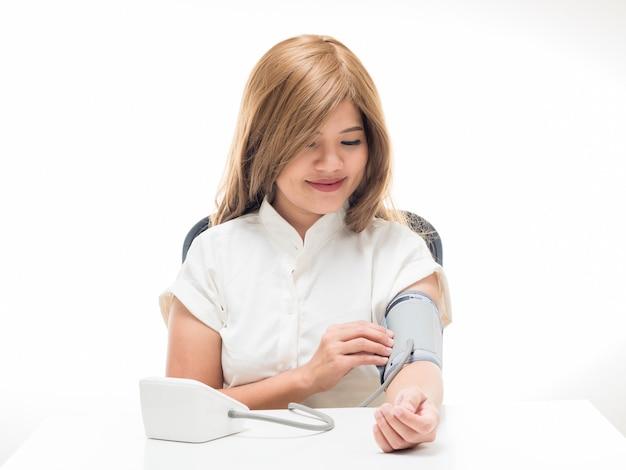 Femme vérifiant la pression artérielle sur fond blanc