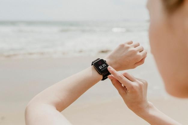 Femme vérifiant sa smartwatch sur la plage