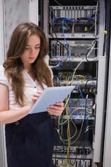 Femme vérifiant les serveurs à l'aide de tablet pc