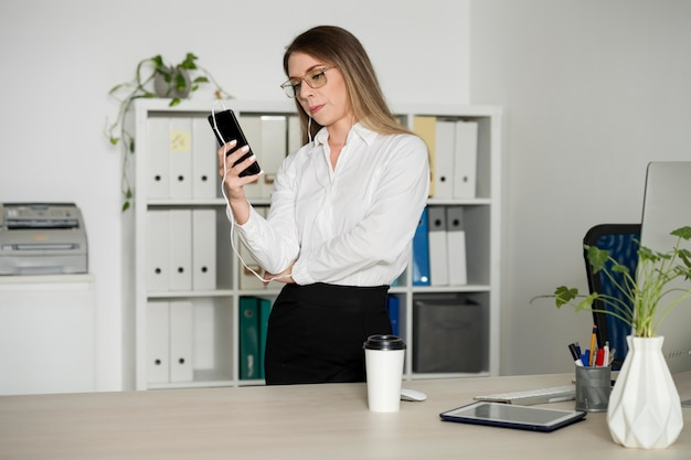 Femme vérifiant son téléphone au travail