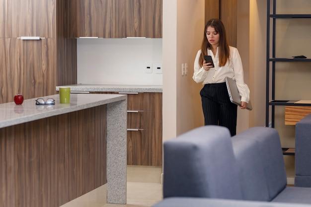 Femme vérifiant son téléphone portable en quittant la maison pour aller travailler femme quittant la maison pour travailler
