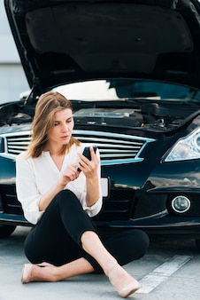 Femme vérifiant son téléphone et sa voiture noire