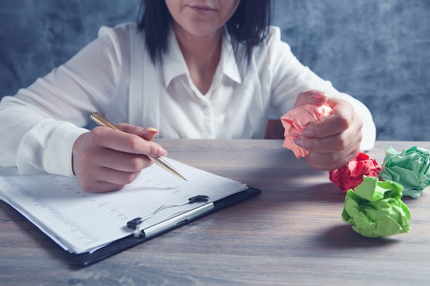 La femme vérifie les papiers et tient le papier froissé