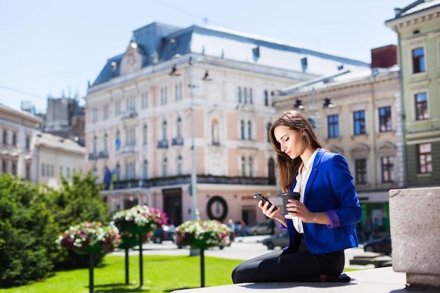 Femme vérifie son téléphone assis avec une tasse de café dans la rue