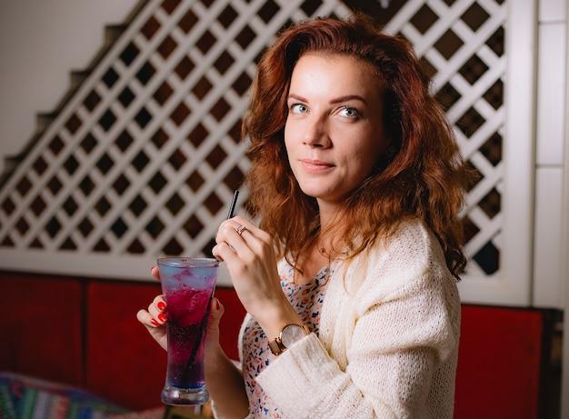 Femme avec verre à cocktail avec tuyau de paille en plastique noir