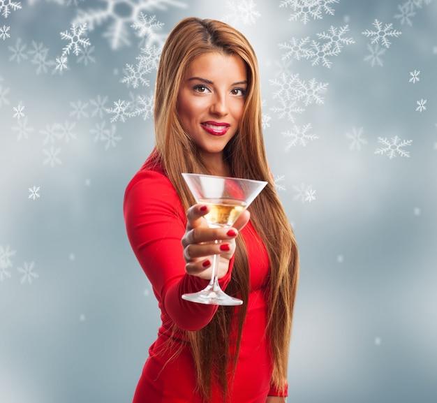 Femme avec un verre dans un fond de flocons de neige