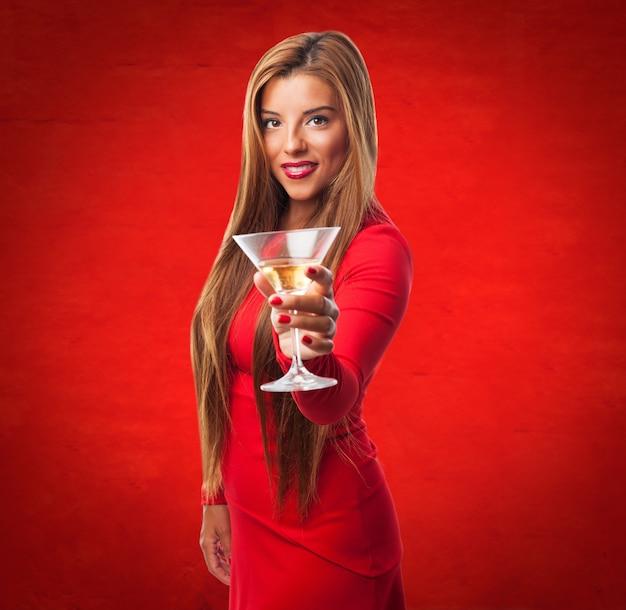 Femme avec un verre dans un fond rouge